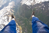 View of a man's legs while sky diving from 14,000 ft over Gudvangen, Norway.