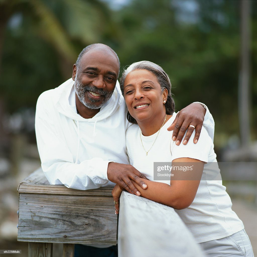 view of a mature couple standing close together smiling : Stock Photo