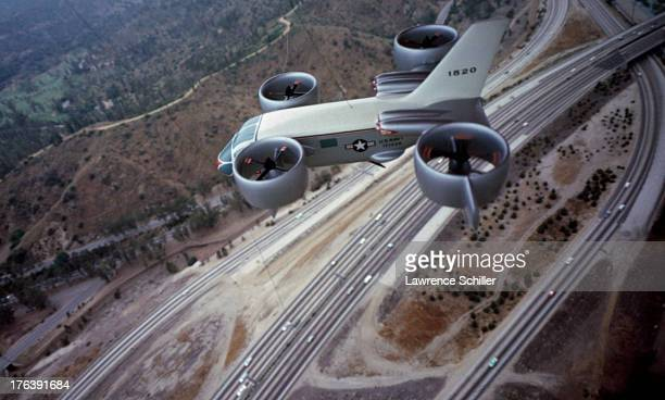 View of a model of a prototype Vertical Takeoff and Landing Vehicle superimposed over a freeway interchange Los Angeles California 1962