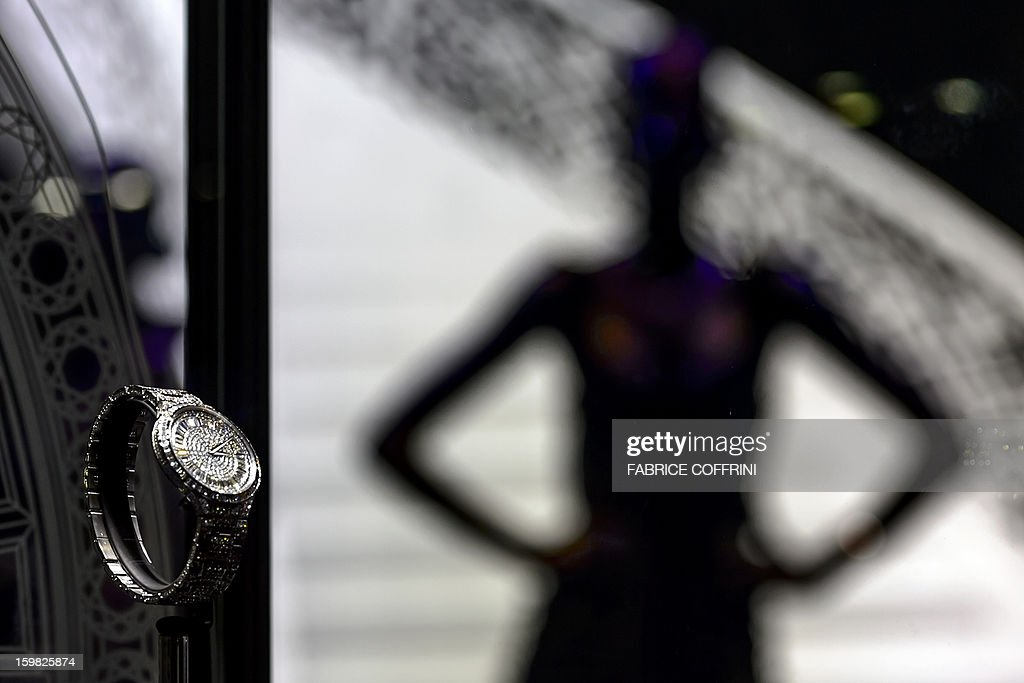 A view of a model posing next to watches by watchmaker Piaget, part of luxury goods group Richemont, during the opening day of the 'Salon International de la Haute Horlogerie' (SIHH), a professional fair in fine watchmaking, on January 21, 2013, in Geneva. Swiss manufacturer of luxury goods Richemont announced that sales met expectations for the third quarter of its 2012 fiscal year at 2.8 billion Euros, up 5% from the preceding year at the constant exchange rate and 9% at the real exchange rate. AFP PHOTO / FABRICE COFFRINI