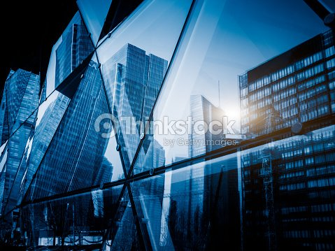 View of a modern glass skyscraper reflecting the buildings around : Stock Photo