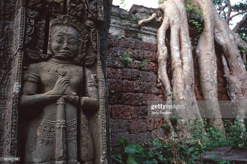 View of a mythical Hindu guardian at a doorway in the Preah Khan temple in the ancient Angkor temple complex. Behind are the roots of a giant tree growing from one of the temple walls..