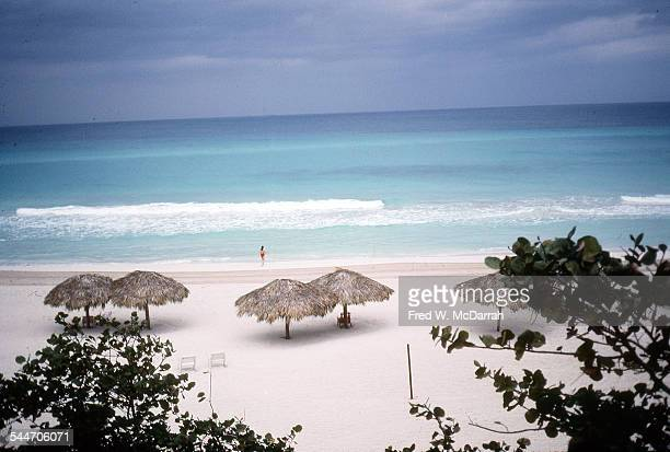 View of a nearly deserted beach at an unidentified resort where one woman in a red swimsuit walks into the surf Varadero Cuba January 1983