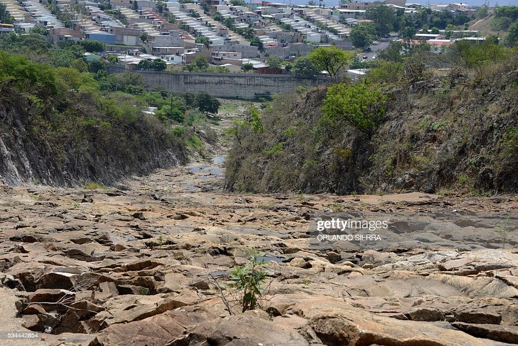 A view of a neighborhood behind a dried-up portion of the Los Laureles reservoir, which along with the La Concepcion and El Picacho reservoirs supplies the Honduran capital Tegucigalpa and its twin city Comayaguela, seen on May 26, 2016. Due to the lengthy drought plaguing Honduras, which has been exacerbated by the El Nino climate phenomenon, the water and sewerage utility SANAA is about to declare a state of emergency in the Honduran capital. / AFP / ORLANDO