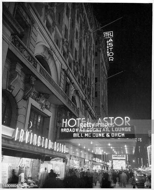 A view of a neon sign announcing Hotel Astor and the kind of entertainment the hotel will have for the evening as crowds of people walk up and down...