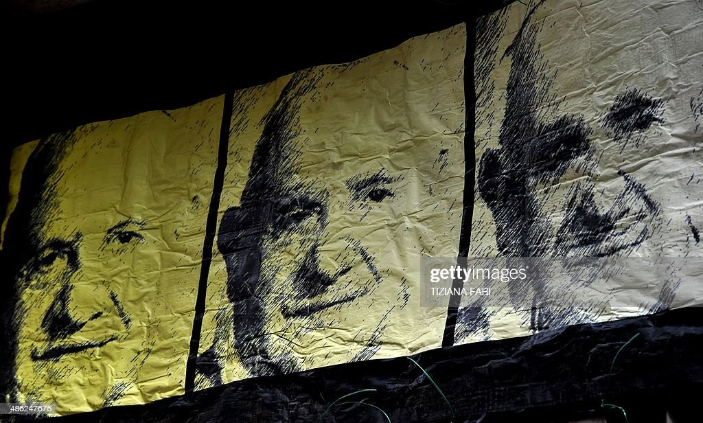 A view of a new work of Italian street artist Maupal, a portrait of the three popes, Pope Francis (C) Pope John Paul II (R) and Pope John XXIII (L) on April 23, 2014 in Rome near the Vatican