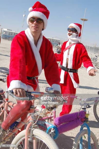 View of a pair of festival goers both dressed in Santa Claus costumes as they stand with bicycles during the Burning Man Festival in the Black Rock...