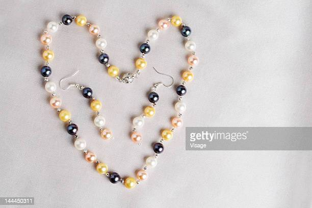 View of a pearl earring and necklace put in a in heart shape