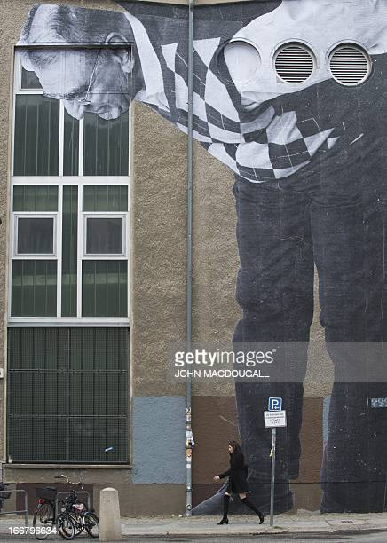 A view of a photograph is posted on a wall by French graffiti artist and selfcoined 'photograffeur' JR as a woman walks down the street in Berlin on...