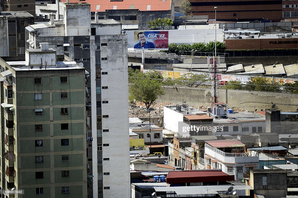 View of a poster of Venezuelan President Hugo Chavez in Caracas on January 4, 2013. Hugo Chavez's top aides have gone on the offensive, accusing the opposition and media of waging a 'psychological war,' as Venezuela's cancer-stricken president battles a serious lung infection. The closing of ranks followed a high-level gathering of top Venezuelan officials in Havana with Chavez, amid growing demands to know whether he will be fit on January 10 to take the oath of office for another six-year-term. AFP PHOTO/Leo Ramirez