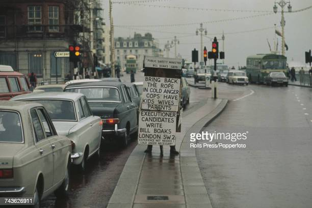 View of a prohanging advocate protesting with a sandwich board on King's Road in Brighton during the annual Conservative Party Conference in the town...