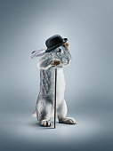 A view of a rabbit with hat and cane on gray studio background