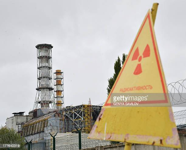 A view of a radioactive sign near a shelter and containment area built over the destroyed 4th block of Chernobyl's old nuclear power plant on August...