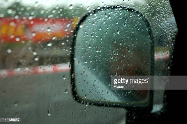 View of a rear view mirror of a car on a rainy day