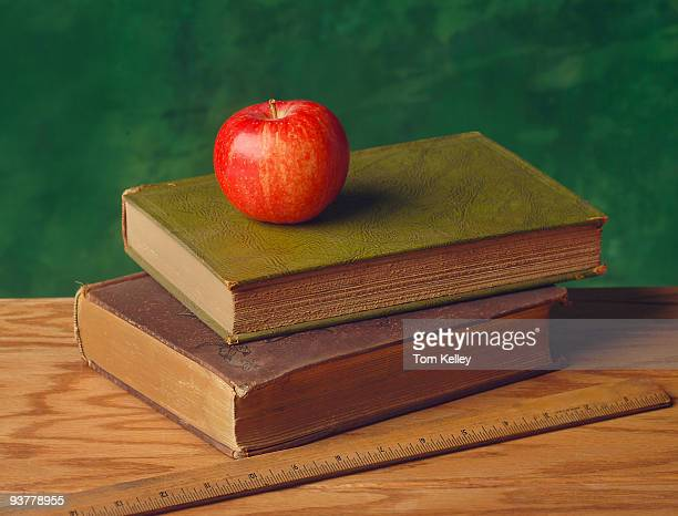 View of a red apple placed on the top of a pair of books themselves on a wooden table next to a ruler seen against a green background 2008