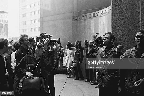 View of a reporters and journalists leaning in with microphones and cameras to record a line of Black Panther Party members as they demonstrate fists...