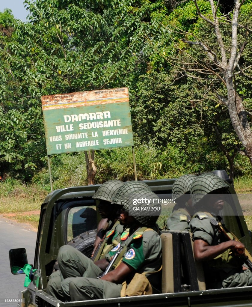 A view of a road sign reading 'Damara, Seductive City, wishes you a warm welcome and an enjoyable stay' as soldiers from the FOMAC multinational force of central African states pass by, between the 'red line' separating regular army soldiers of the Central African Republic and rebels from the SELEKA coalition, near Damara, on January 2, 2013. The commander of the multinational African force FOMAC warned rebels in the Central African Republic against trying to take the key town of Damara, saying it would 'amount to a declaration of war'. Damara is the last strategic town between the Seleka rebel coalition and the capital Bangui, after the rebels seized much of the country in a three-week advance that began in the north and has brought them to within 160 kilometres (100 miles) of the capital, in the south.