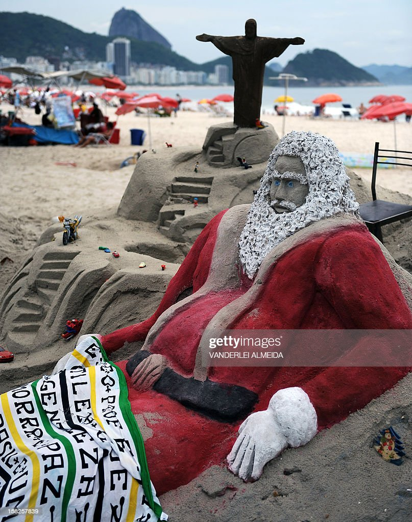 View of a sand sculpture depicting Santa Claus at Copacabana beach in Rio de Janeirro, Brazil on December 12, 2012. High temperatures -35 to 38 degrees celcius- during the end of the spring, have taken citizens and tourists to the beaches of Rio de Janeiro.