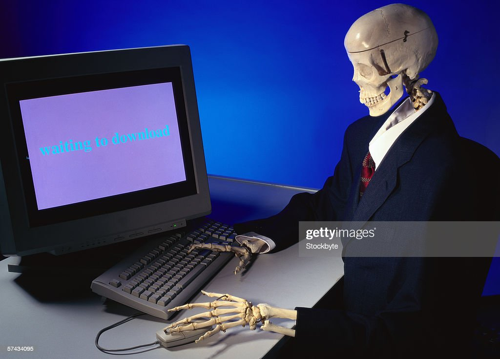 view of a skeleton sitting in front of a computer : Stock Photo