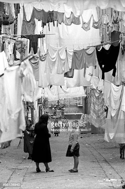 View of a sloping alley in the Old Town the clothes hanging on wires occupy most of the sight a child smiling and an elderly woman stand in the...