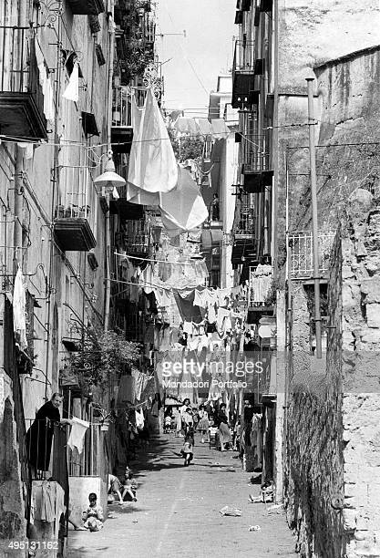 View of a sloping street in the Old Town with the clothes hanging on wires stretched from houses on the two sides of the road occupying most of the...