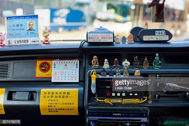 View of a taxi drivers dashboard in a Hong Kong Taxi showing talismans and charms placed presumably for good luck or as an extra insurance policy