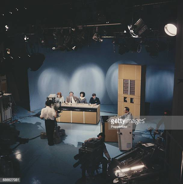 View of a television studio with English broadcaster David Jacobs on right presenting an edition of the BBC television show Juke Box Jury with guests...