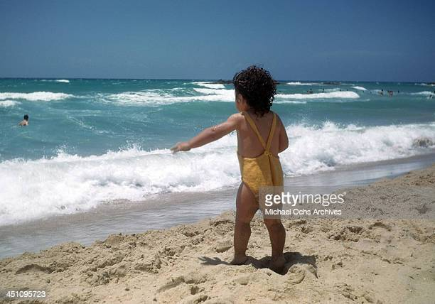 A view of a toddler walking near the surf on a beach in Beirut Lebanon