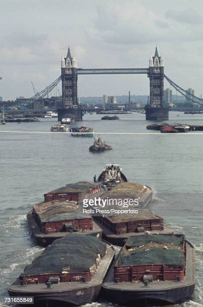 View of a tugboat hauling lighters or barges downriver along the River Thames through the Pool of London to Tower Bridge in August 1971