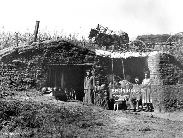 View of a typical sodhouse wagon load of sod stands on the hillside in the rear of the dugout to repair the roof Nebraska late 19th century The team...