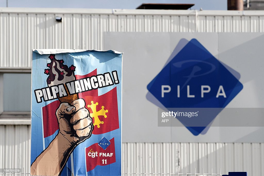 A view of a union poster hanging next a factory sign at the Pilpa ice cream factory in Carcassonne, southern France, as workers take part in surveillance rounds to stop the new factory owner from taking or dismantling factory equipment and machines, on December 27, 2012. 112 workers face the threat of being layed-off since July 2012 when the factory's owner sold the site to the R&R ice cream company and have struggled to keep the site and its jobs ever since. As the workers await court rulings pertaining to the factory site and its future, workers say they are being vigilant and have instituted rounds and a night guard to make sure R&R does not leave with the machines and equipment, thereby making it impossible for workers to consider continuing production at the site.