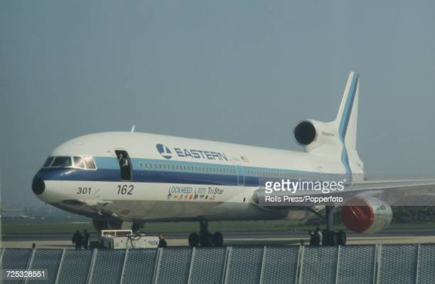 View of a United States built Lockheed L1011 TriStar threeengine wide body civilian jet aircraft in Eastern Airlines livery being towed by a tractor...