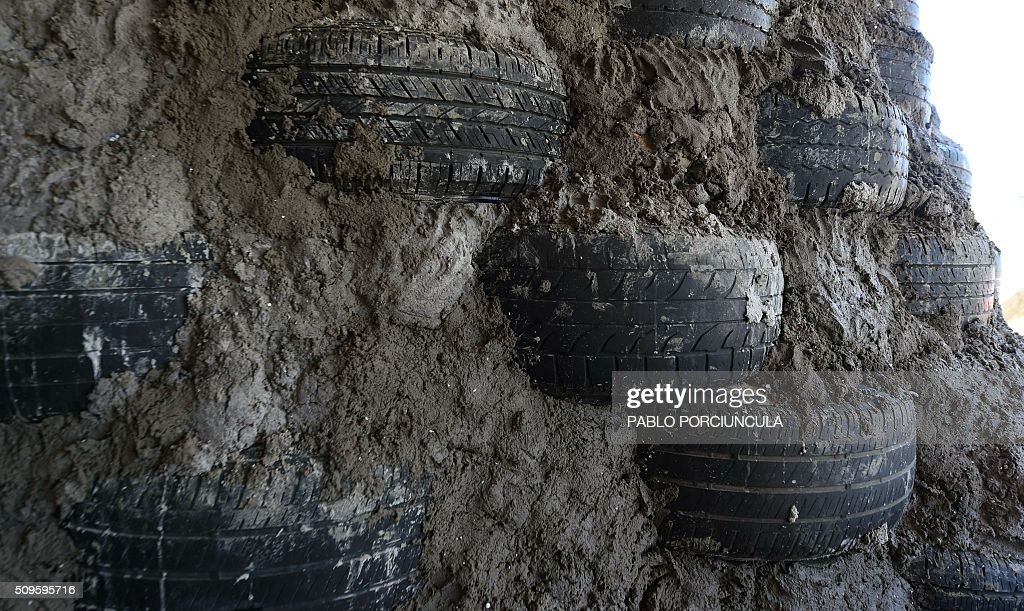 View of a wall made of tyres during the construction of an auto-sustainable elementary school in Jaureguiberry -80 km east of Montevideo, Uruguay- on February 11, 2016. US architect Michael Reynolds, founder of Earthship Academy, gives training to 100 students from 30 countries (most of them architects) in Earthship design principles, construction methods and philosophy, to build the first school of this kind in the world. AFP PHOTO / PABLO PORCIUNCULA / AFP / PABLO PORCIUNCULA
