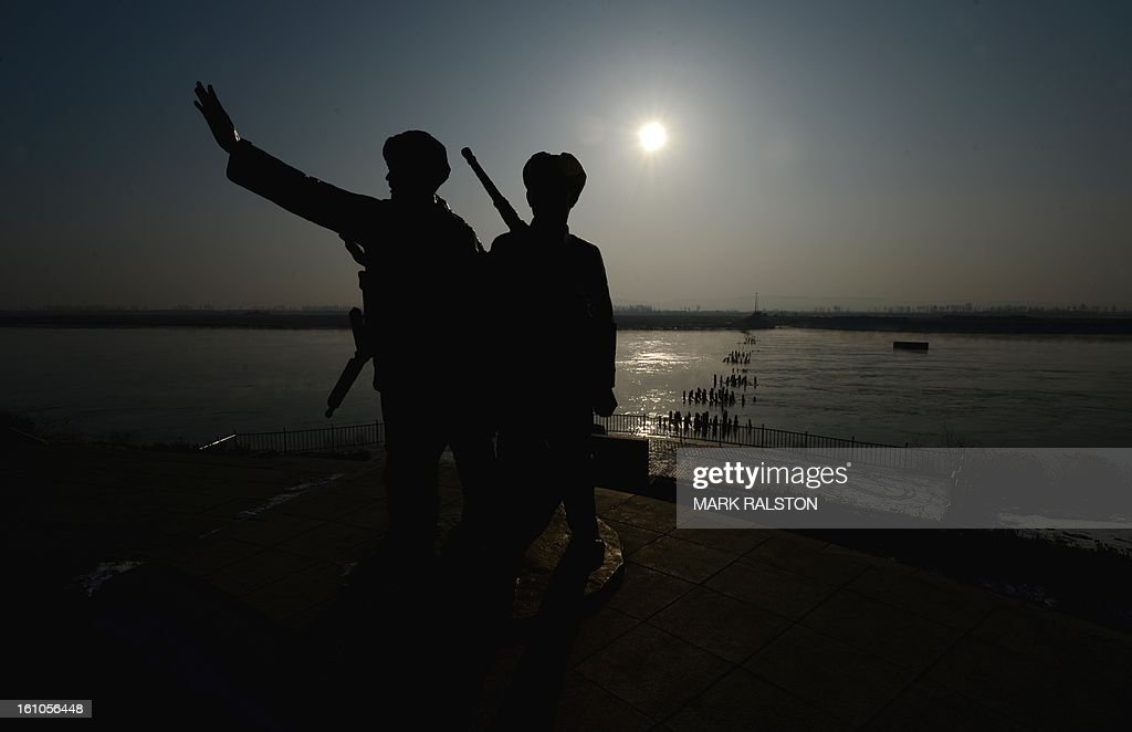 View of a war memorial showing soldiers from the Korean war and the Jinhai Bridge bombed by the US Air Force in 1951 that was one of the links across the Yalu River between the North Korean town of Sinuiju and the Chinese town of Dandong on February 9, 2013. US Secretary of State John Kerry warned that North Korea's expected nuclear tests only increase the risk of conflict and would do nothing to help the country's stricken people. The country has vowed to carry out a third nuclear test soon, and concerns have been raised over the type of fissile material used in the device. AFP PHOTO/Mark RALSTON