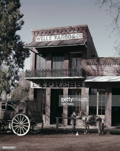 View of a Wells Fargo office and gold miner standing outside 1990