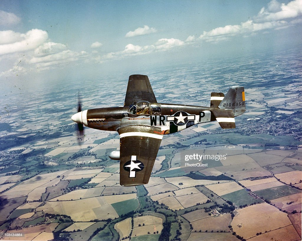 View of a white-nosed North American P-51B Mustang, of the 8th Air Force, flying over the fields of England, ca.1940s.
