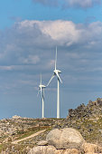 View of a wind turbines on top of mountains, blue cloudy sky as background in Portugal