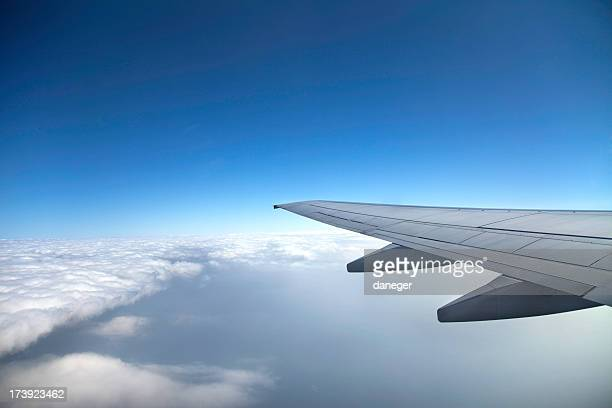 A view of a wing of a jet and the clouds from the inside