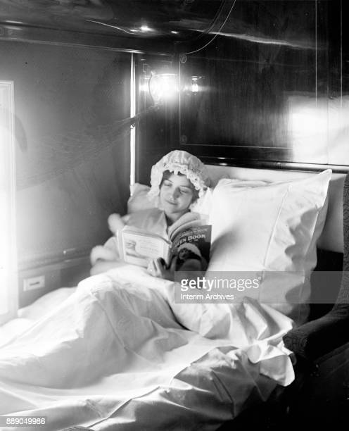 View of a woman as by electric light she reads an issue of Green Book magazine in bed in a train sleeper car circa 1915
