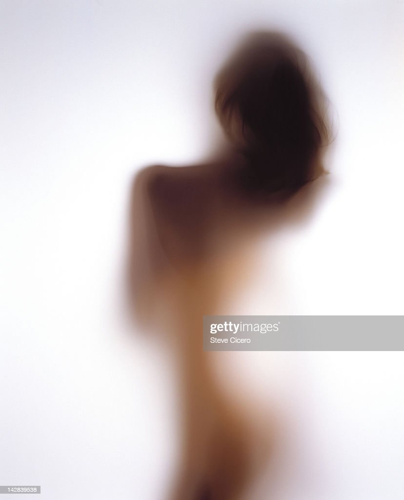 View of a woman behind frosted glass : Stock Photo