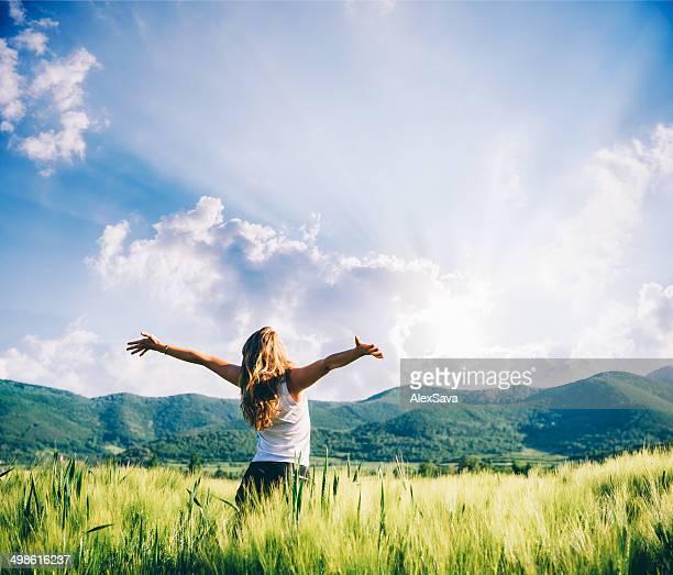 Vista de uma mulher no campo de trigo beeing feliz