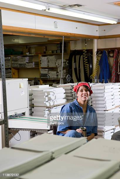 View of a woman sitting down during a coffee break while working in a warehouse
