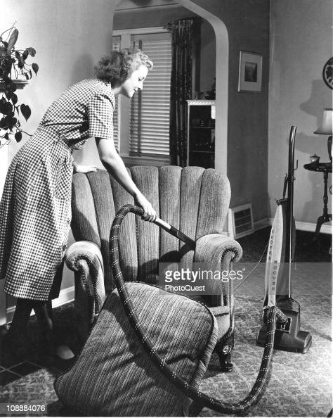 View of a woman using a Hoover vacuum cleaner to clean an armchair 1950