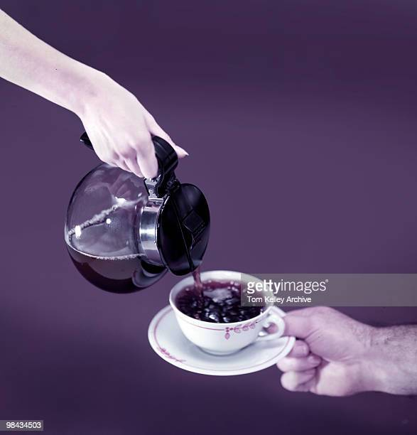 View of a woman's hand as it pour coffee from a carafe into a cup on a saucer held by a man's hand 1952
