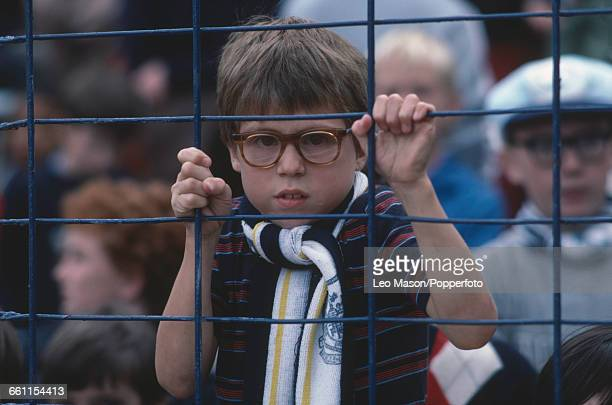 View of a young boy football fan and supporter of Tottenham Hotspur holding on to the bars of a metal crowd control fence at a first division...