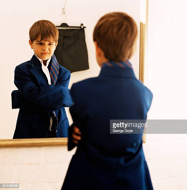 view of a young boy (8-10) standing in front of a mirror wearing an oversize coat