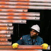 view of a young construction worker peeping from s hole in a metal wall