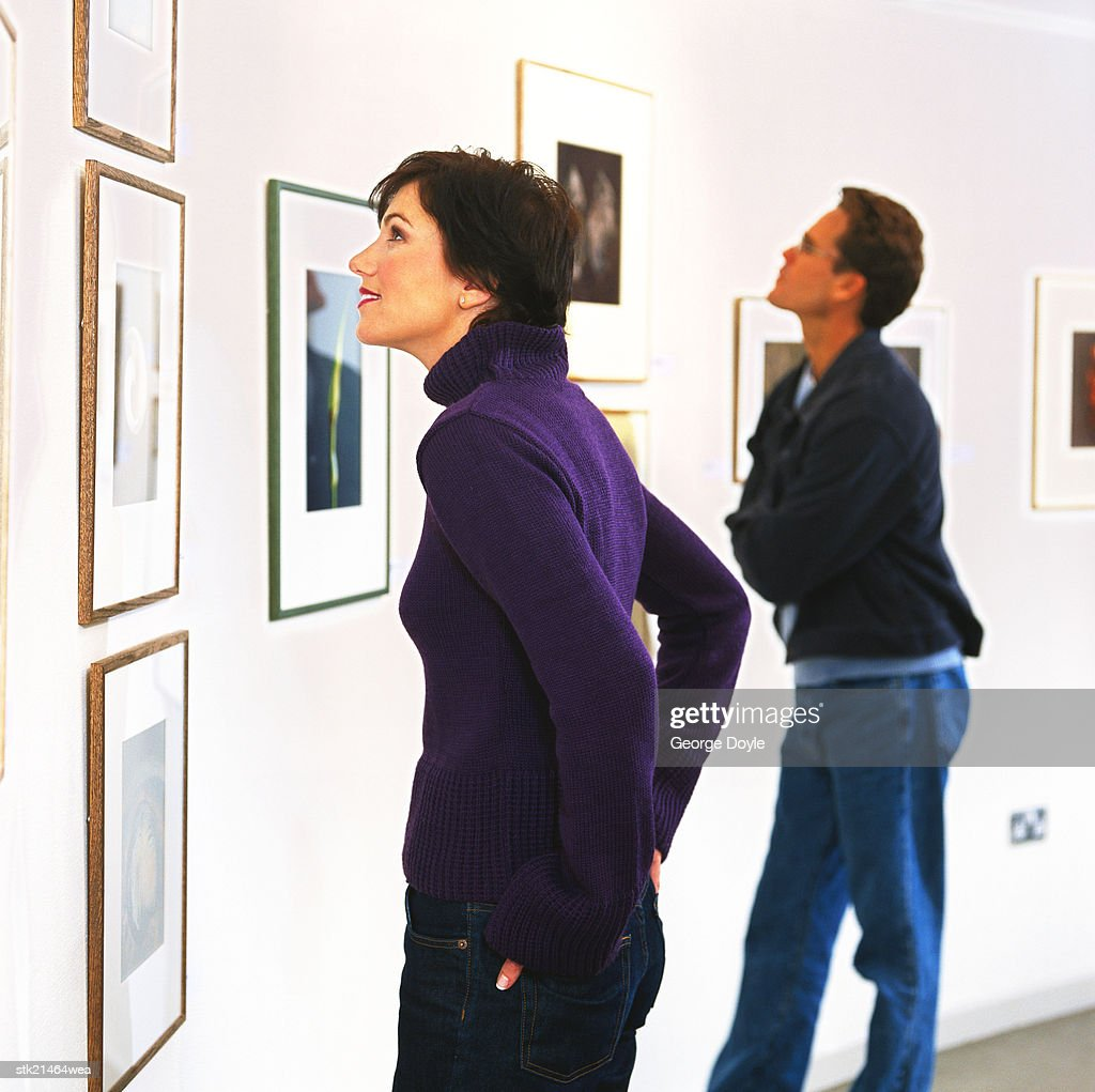 view of a young couple viewing art hung on the wall in a gallery : Stock Photo