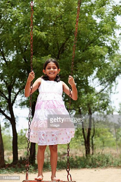 View of a young girl playing on a swing