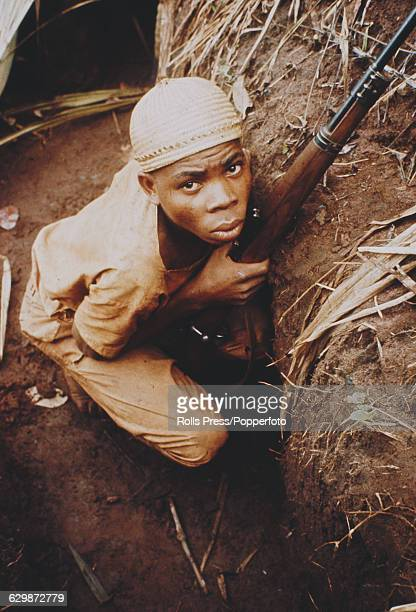 View of a young male soldier from the Republic of Biafra crouching in a foxhole with a rifle during the Nigerian Biafran civil war in Nigeria in...